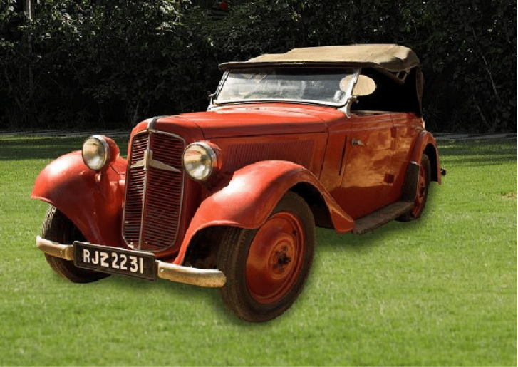 A red vintage car parked in a grassy field  Description automatically generated